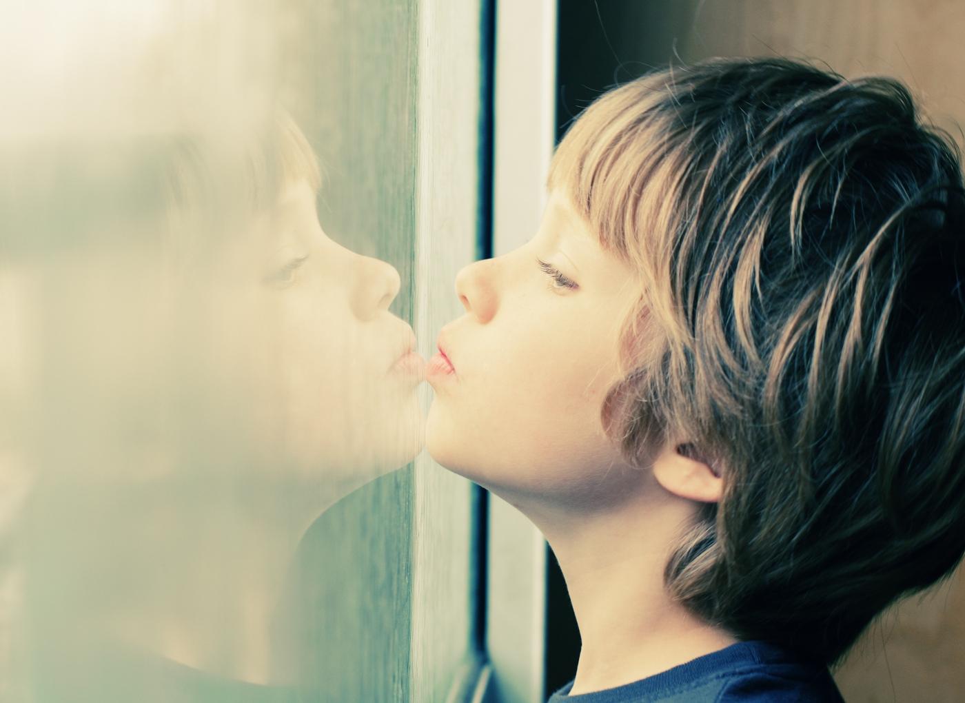Criança com síndrome de Aperger a olhar pela janela