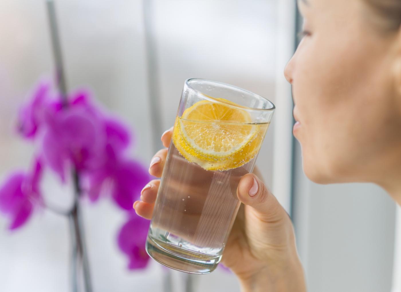 Mulher a beber água com limão