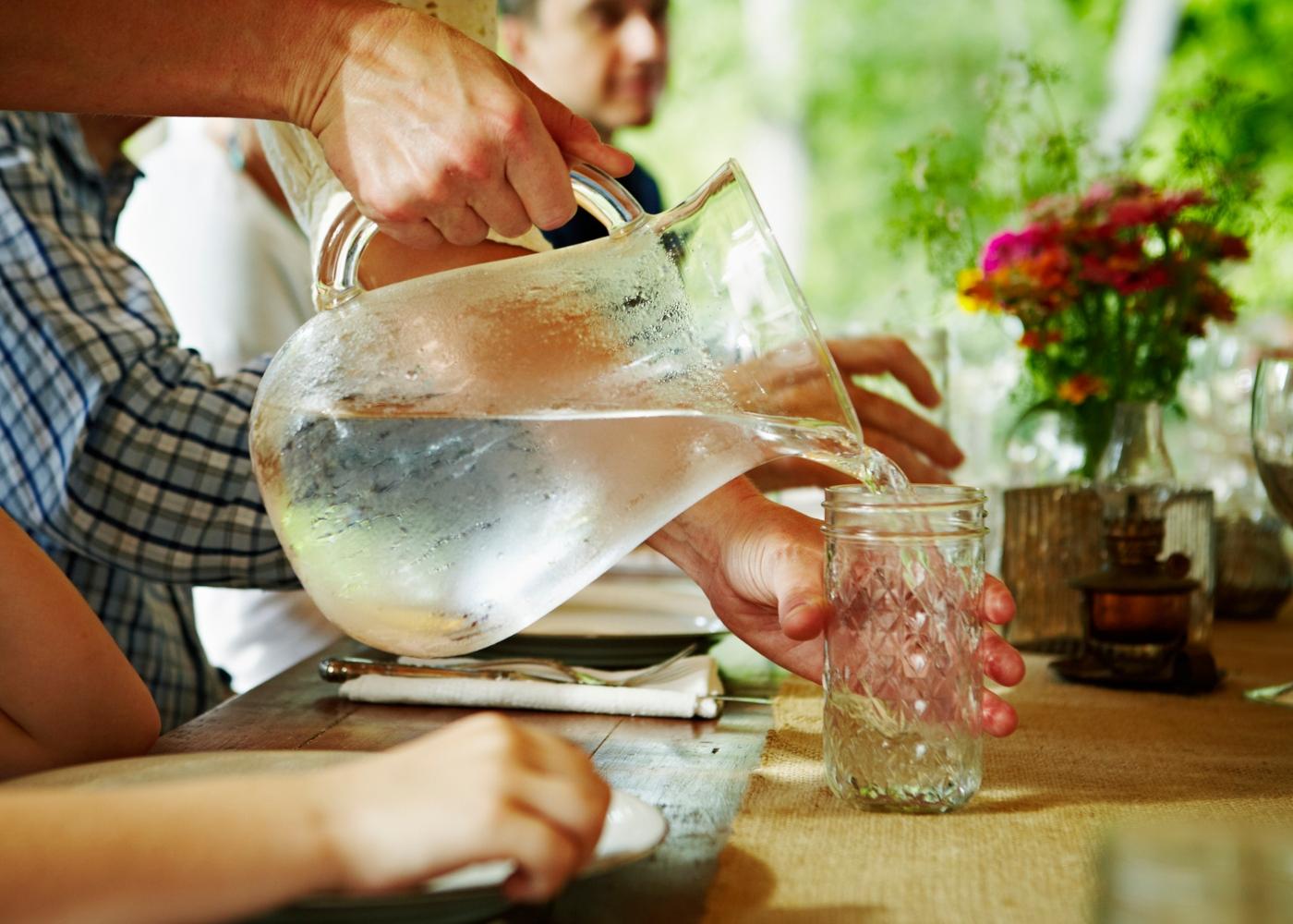 Homem a servir água a clientes num restaurante