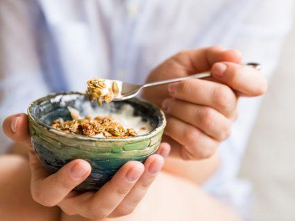O que comer durante o dia para não chegar à noite com muita fome: mulher a comer iogurte com cereais