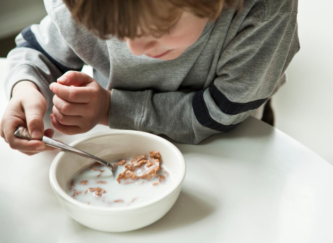Alimentos ricos em vitamina D: criança a comer cereais