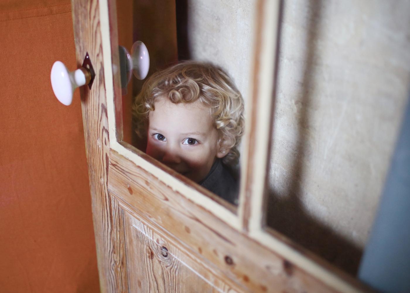 Enurese noturna: menino envergonhado a esconder-se atrás da porta
