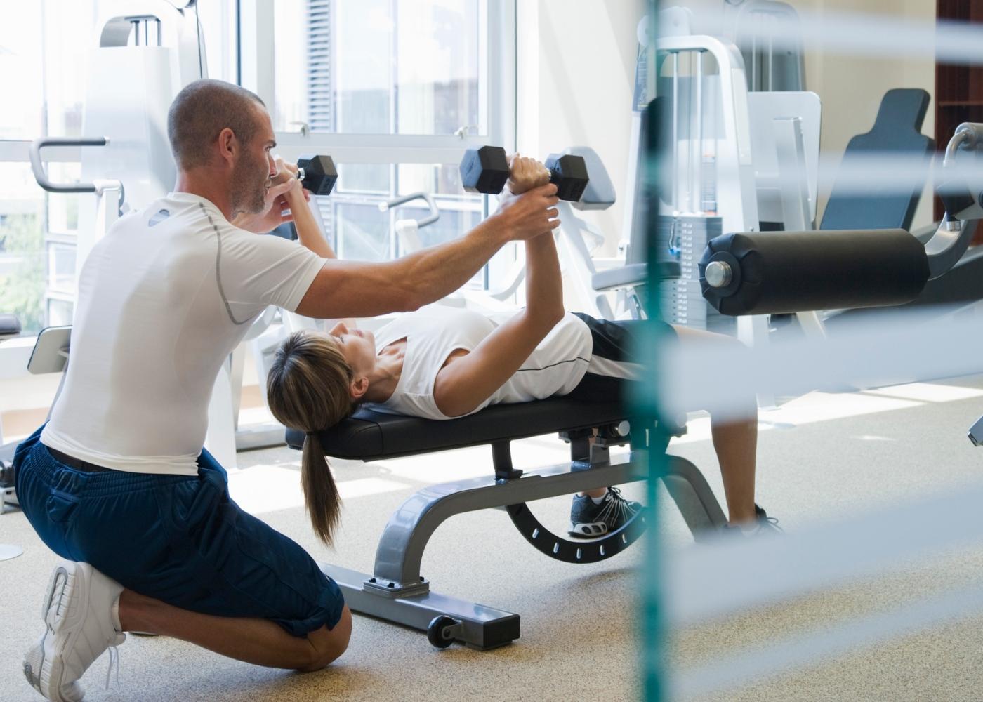 Ganho de massa muscular: mulher a treinar com PT