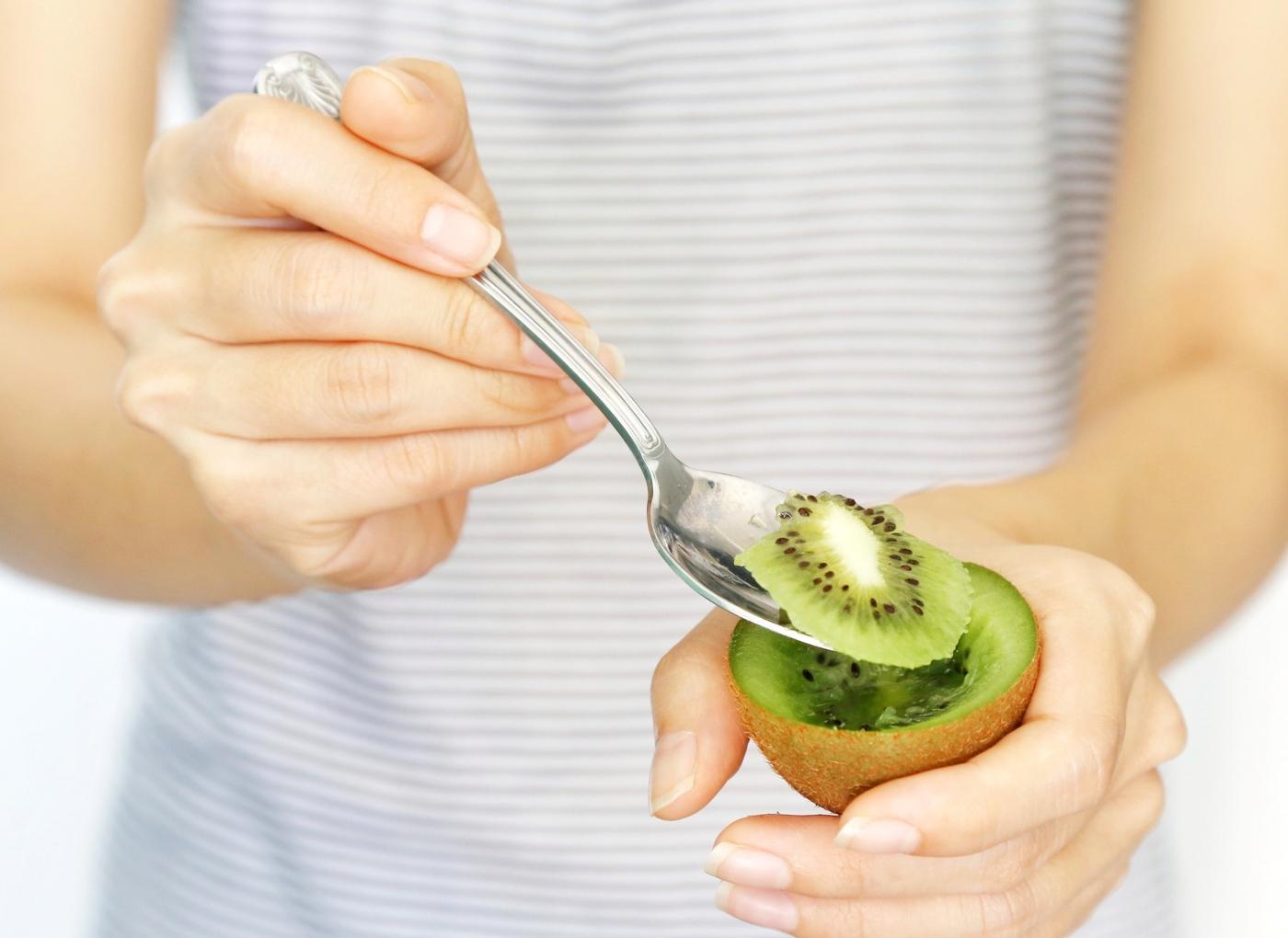 Mulher a comer kiwi