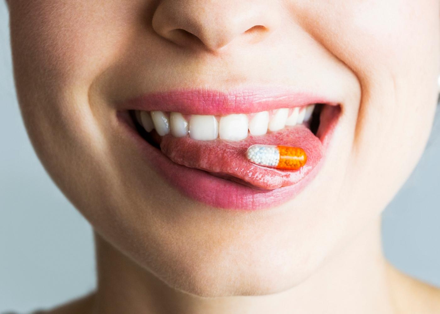 Mulher a tomar suplemento de vitamina C