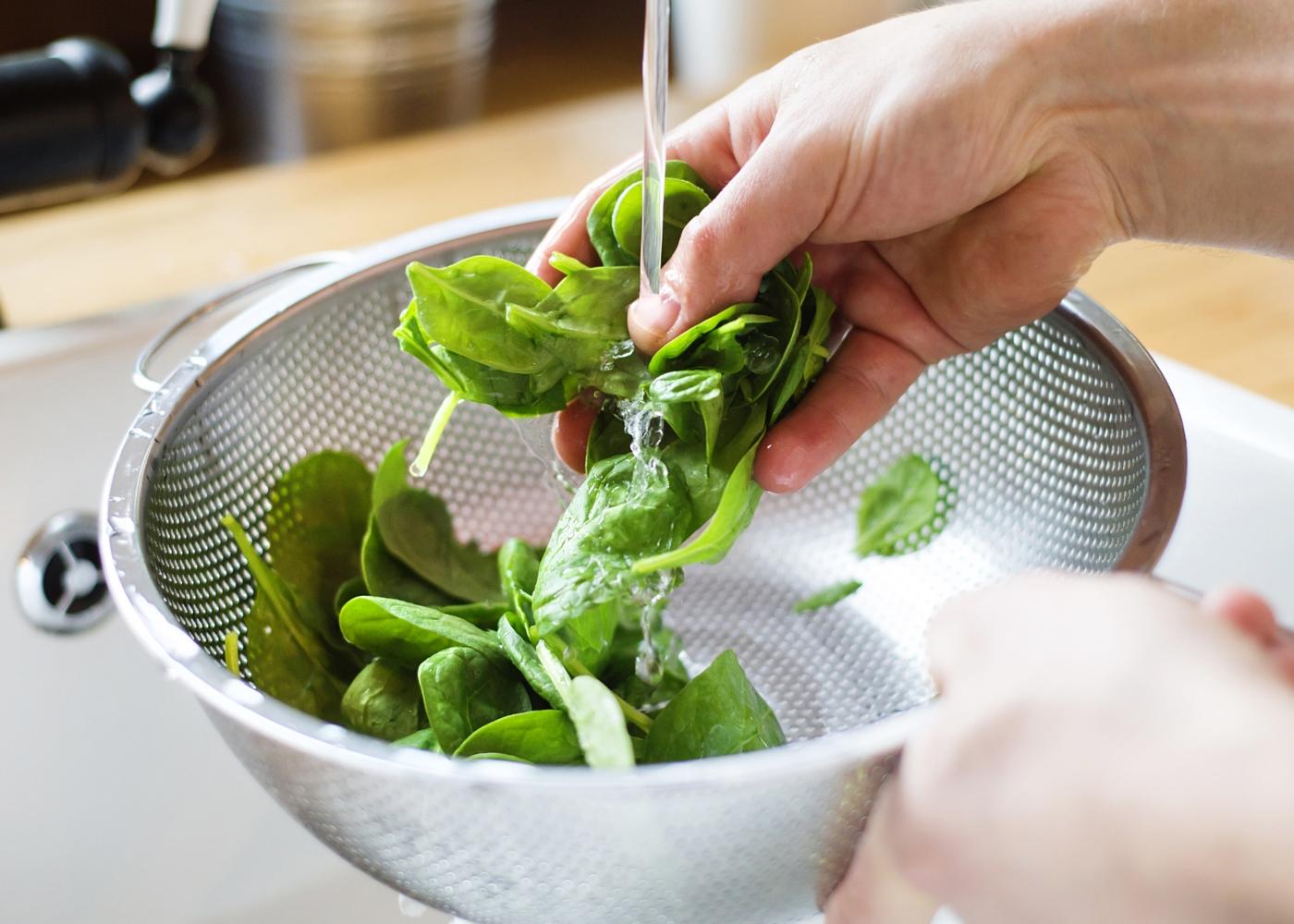 orientações na área da alimentação: mulher a lavar legumes