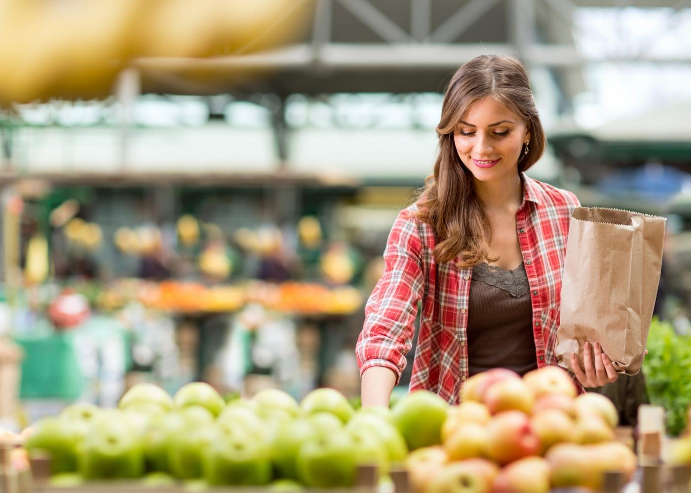 Alimentos que deve e não deve comprar: mulher a escolher frutas e legumes no supermercado
