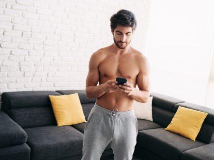 Homem a selecionar apps para treinar em casa no seu smartphone