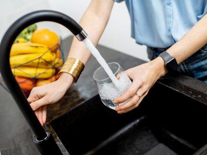beber mais água em casa: mulher a encher copo de água da torneira