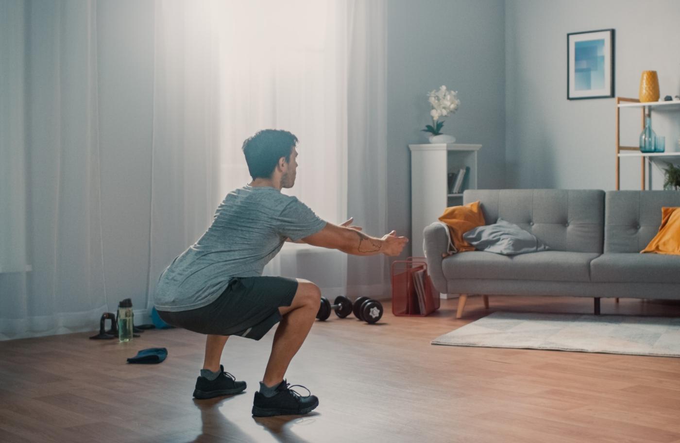 Tipos de agachamentos: homem a fazer bodyweight squat em casa