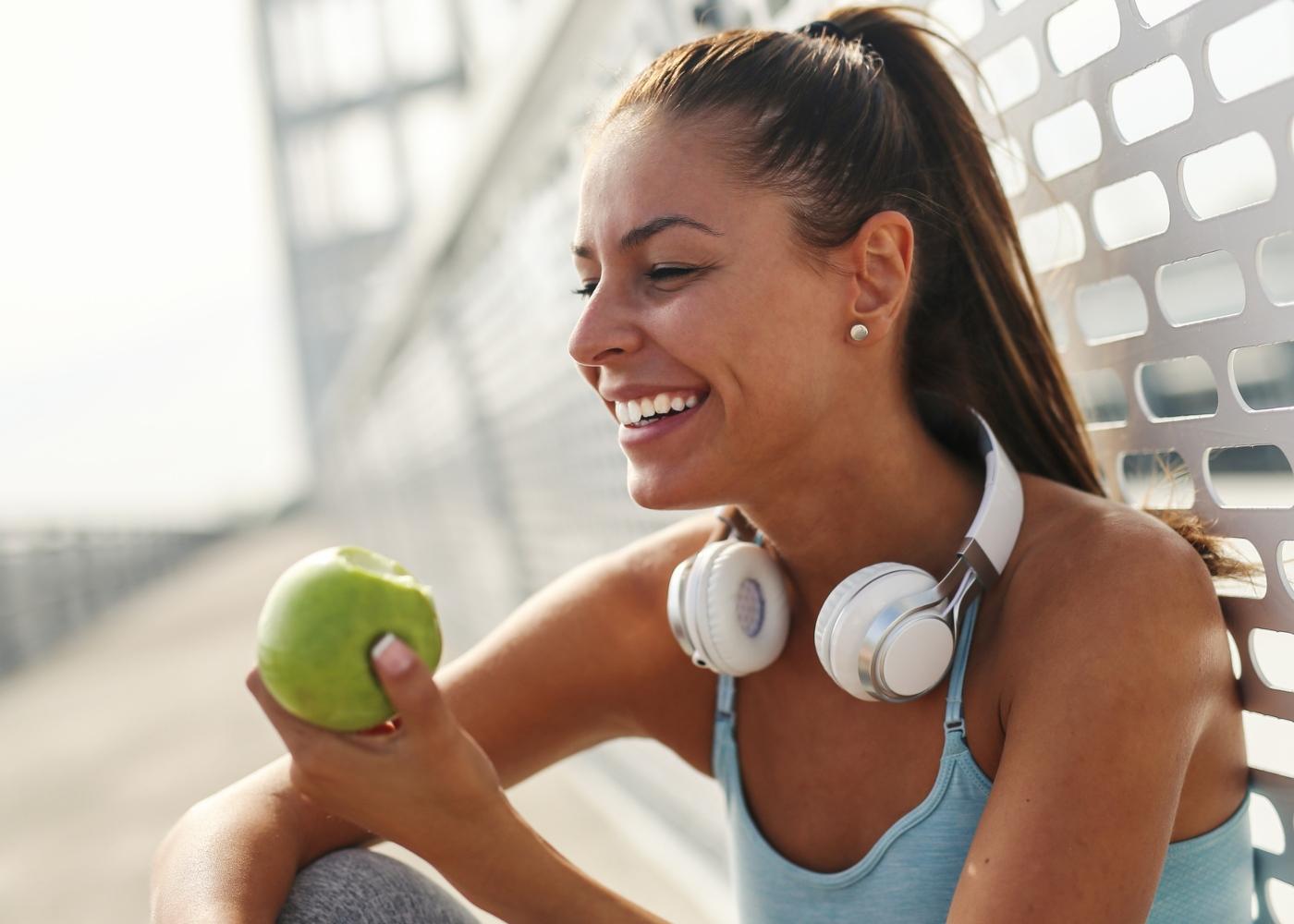 O que comer antes do treino: mulher a comer uma maça