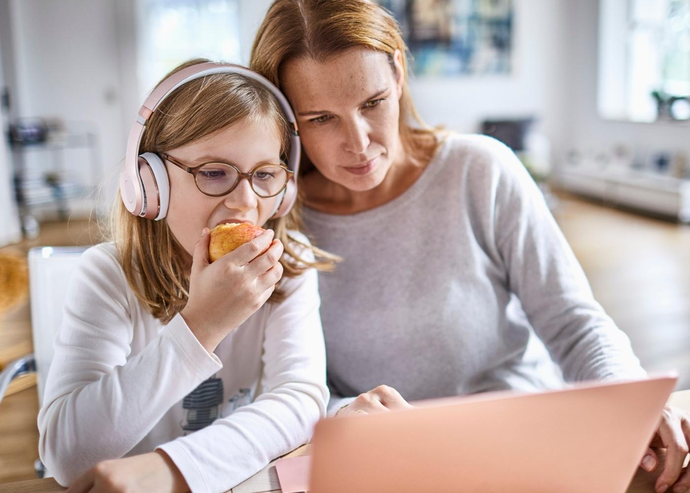 Atividades para fazer em casa e família: mãe e filha a ver conteúdos educativos