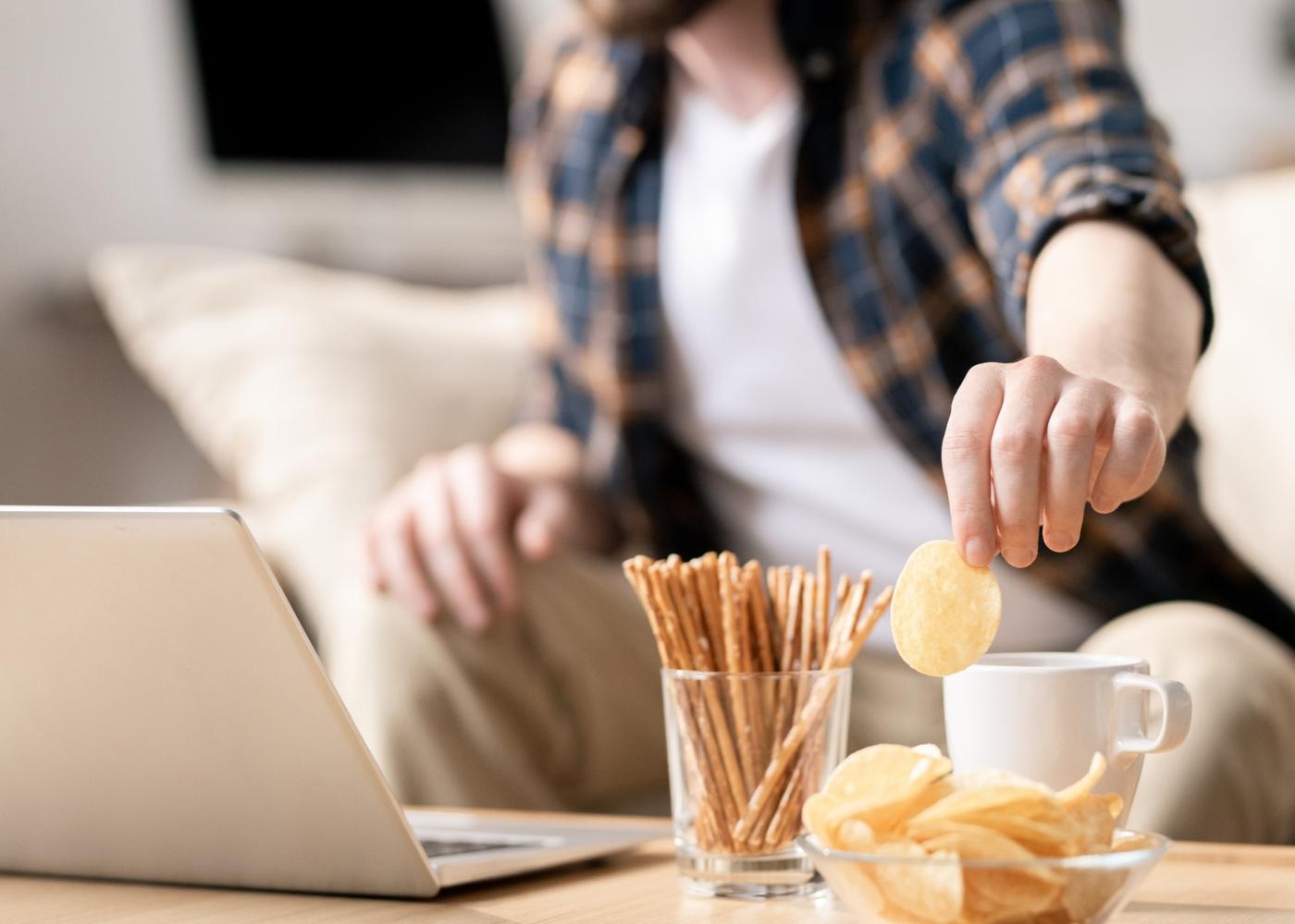 Como controlar vontade de comer em casa: homem a comer snacks