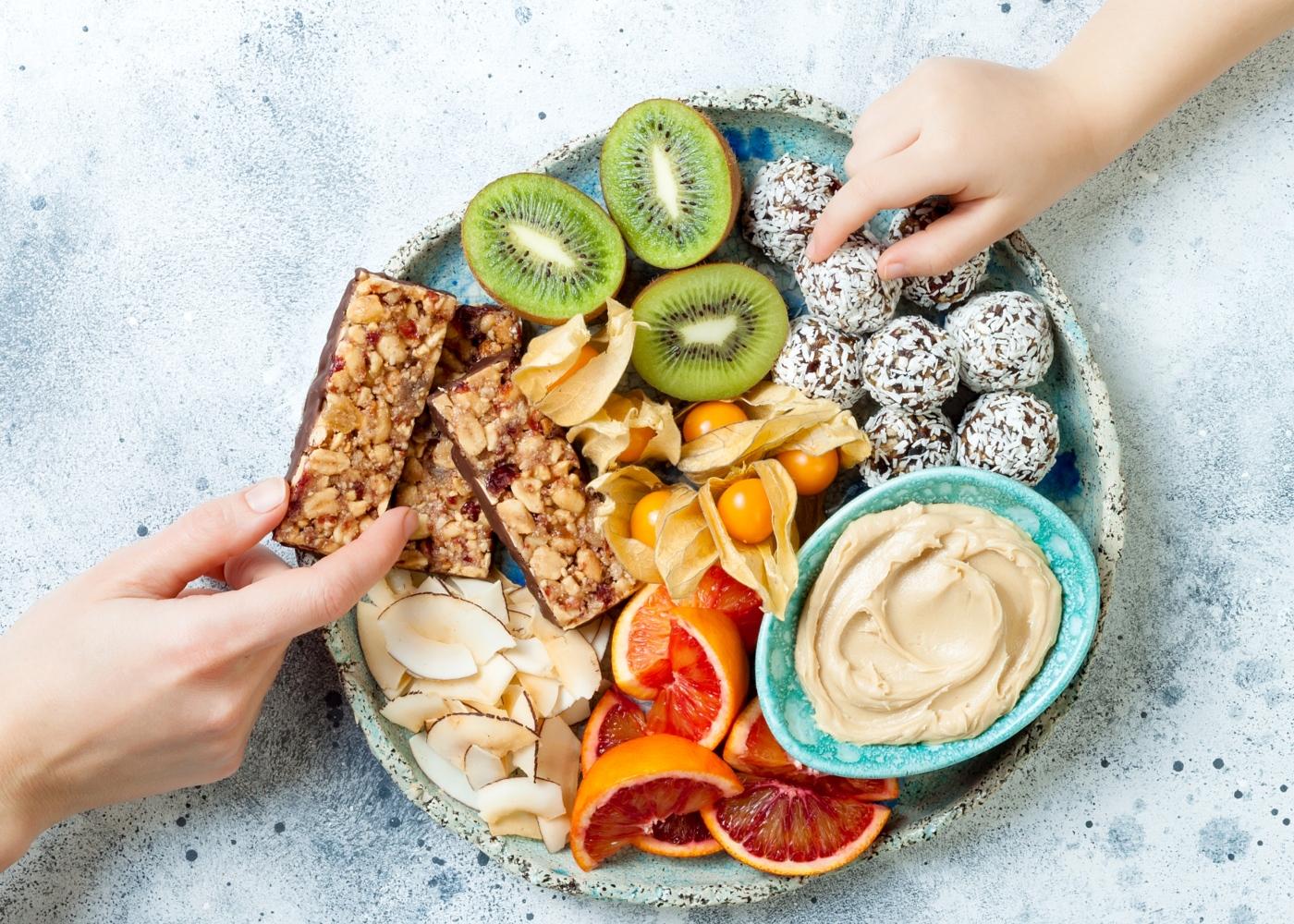 Como controlar a vontade de comer em casa: mãe e filha a comerem snacks