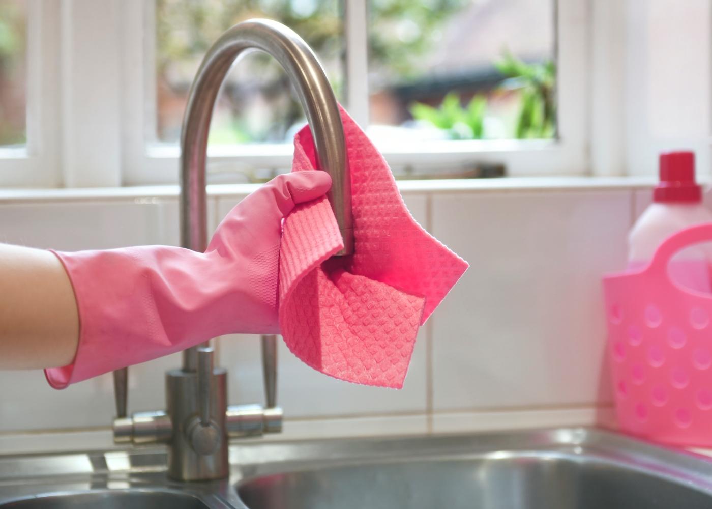 Quanto tempo permanece o coronavírus em superfícies: mulher a limpar a cozinha