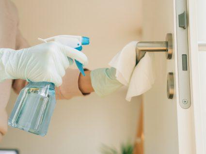 Quanto tempo permanece o coronavírus em superfícies: mulher a limpar puxadores das portas