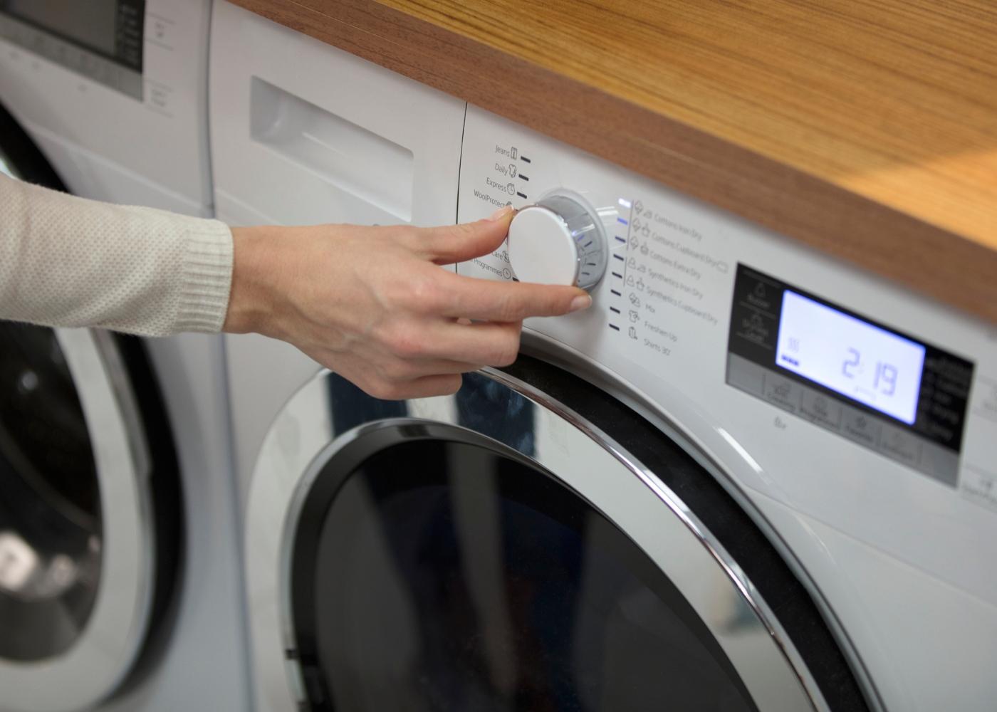 Mulher a lavar roupa na máquina