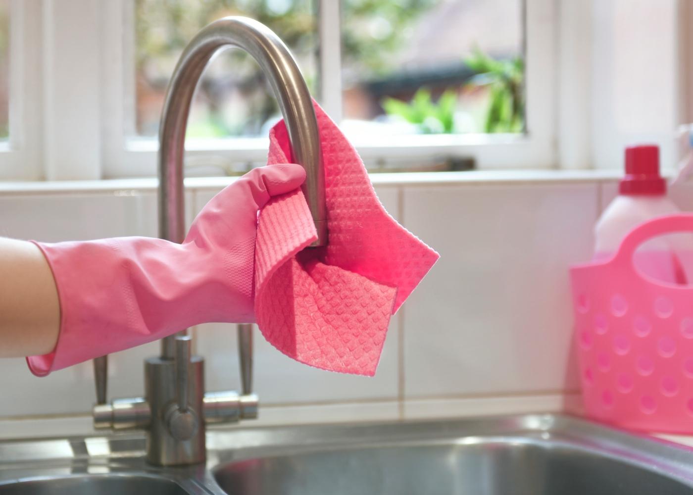 como desinfetar superfícies: mulher a limpar a cozinha