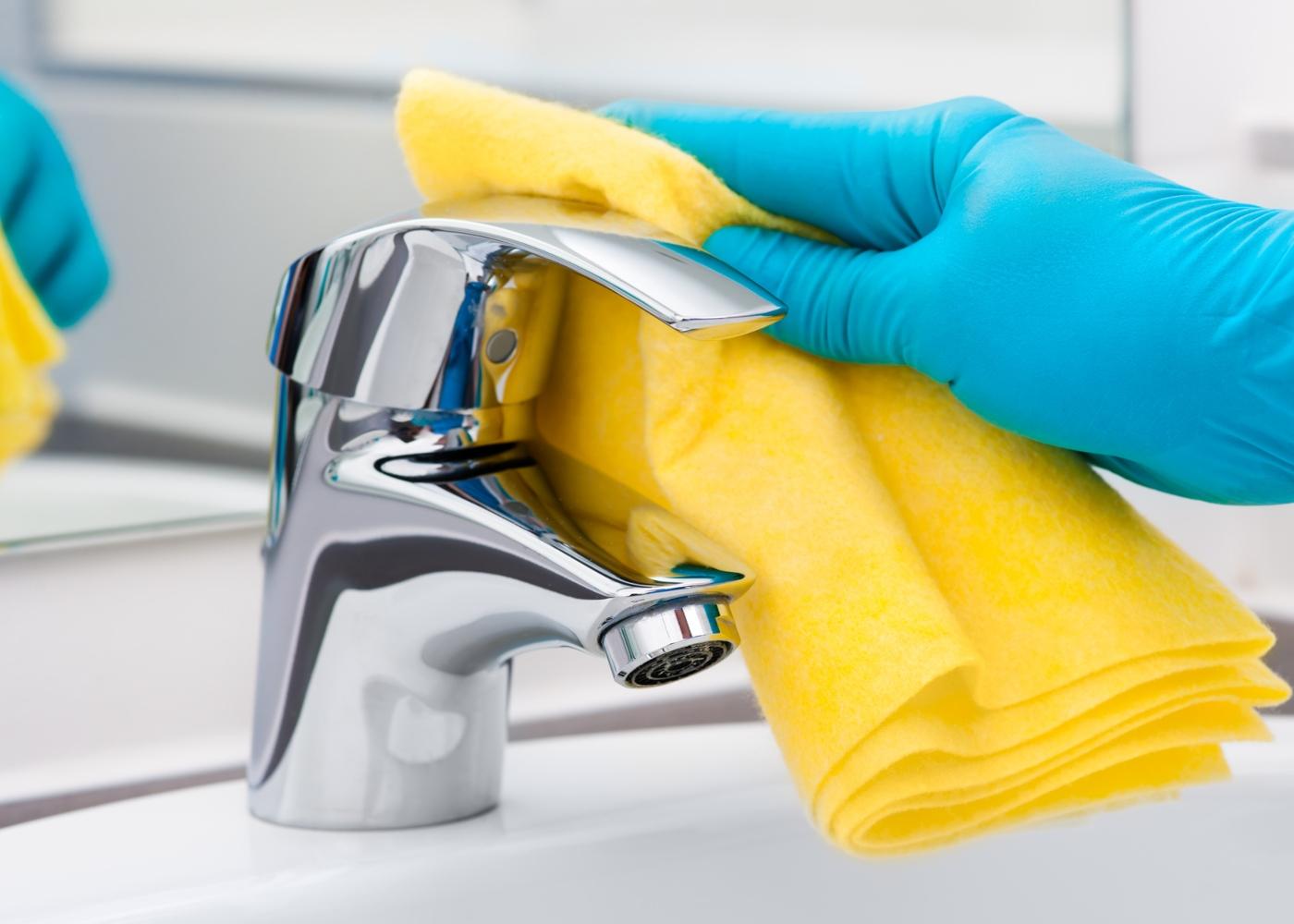 Como desinfetar objetos: mulher a limpar torneiras da casa de banho
