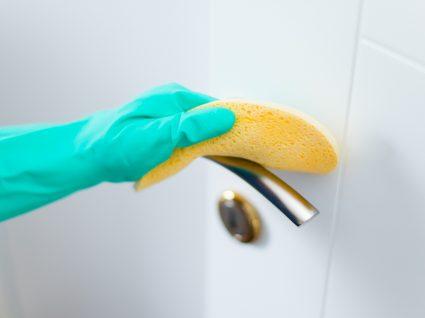 como desinfetar superfícies: mulher a limpar puxador de porta