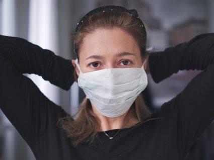 Mulher a colocar máscara de proteção reutilizável
