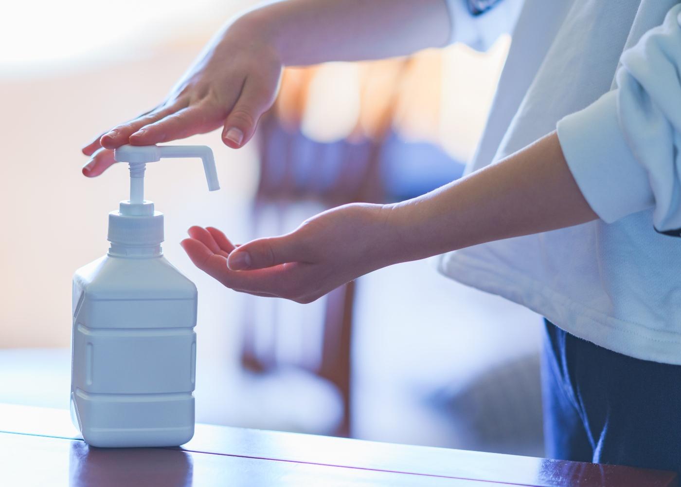 Mulher a desinfetar as mãos com solução alcoólica