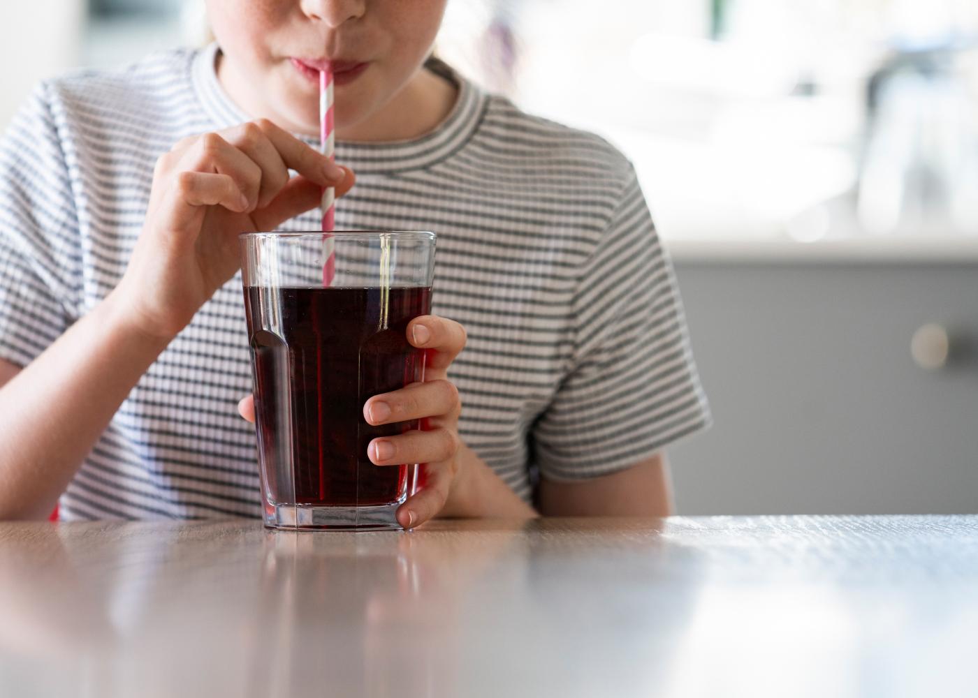 menino a beber refrigerante com açúcar num copo de vidro