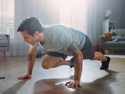 Exercícios para perder gordura abdominal: homem a fazer moutain climbers em casa