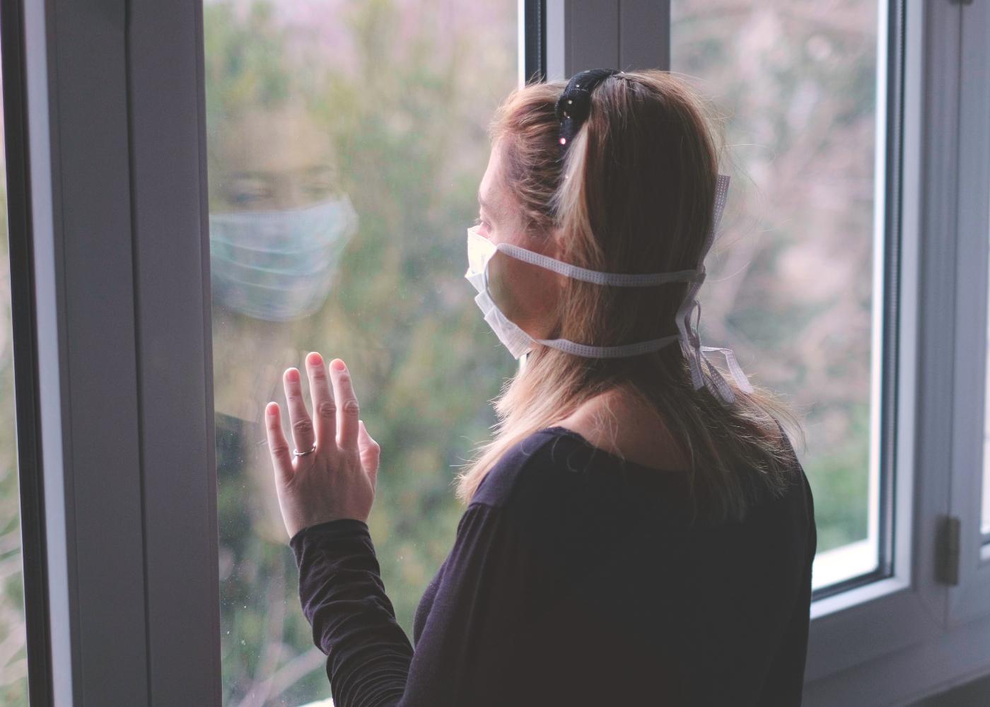 mulher com máscara de prevenção à janela