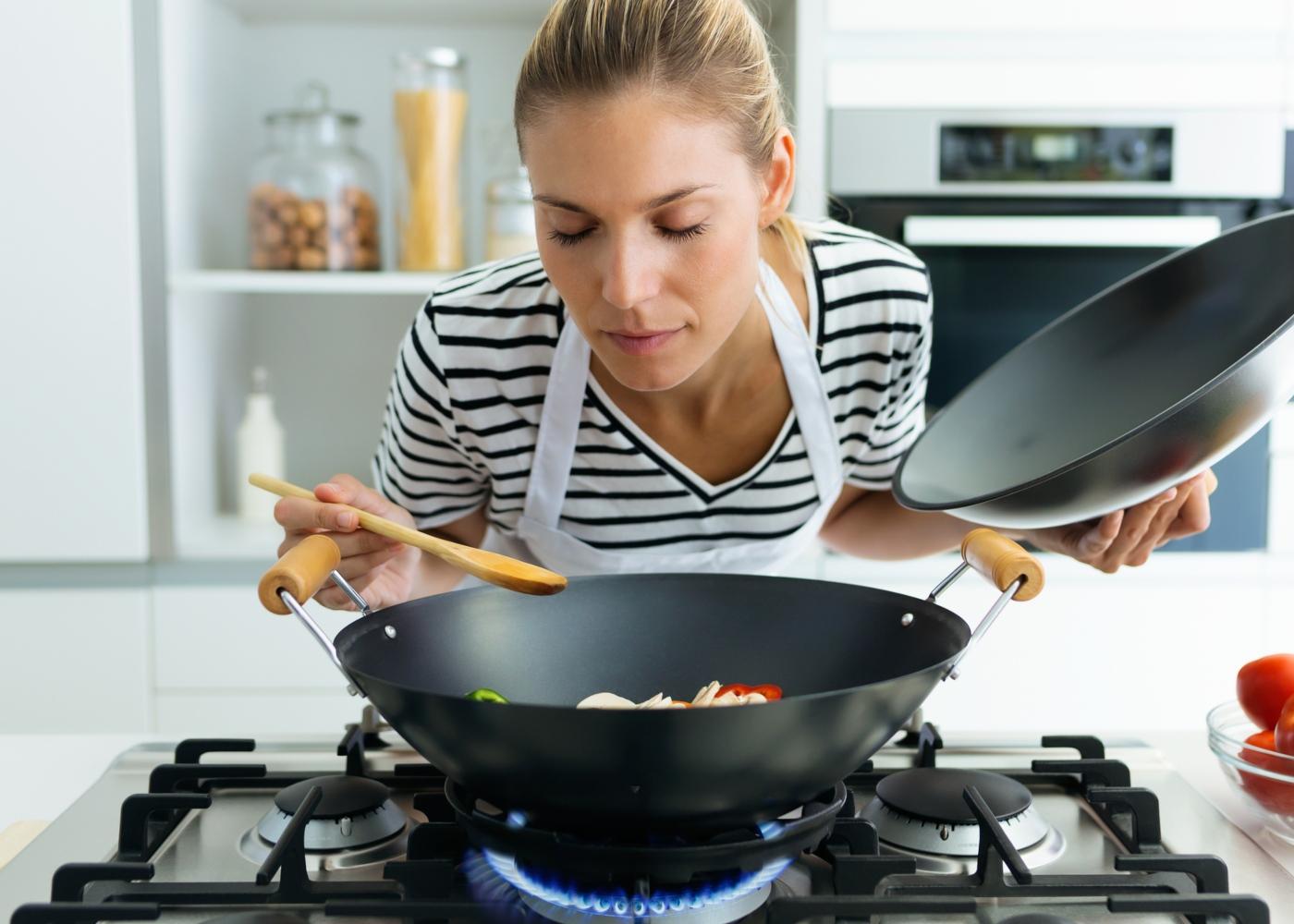 Ementa semanal: mulher a preparar refeição em casa