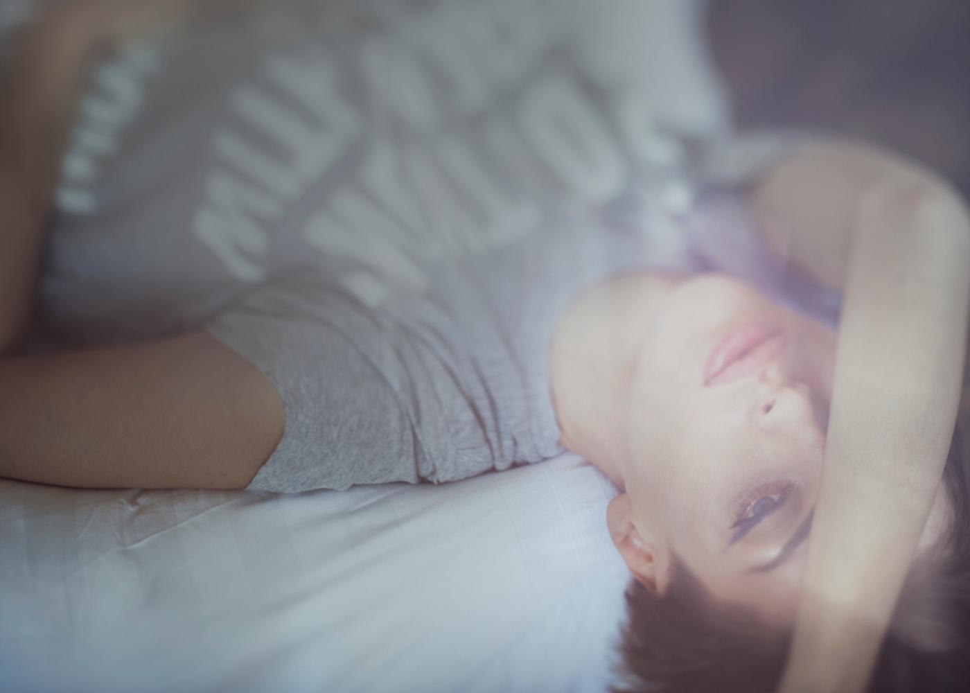Proteger a saúde mental em caso de isolamento: mulher deitada na cama em período de quarentena