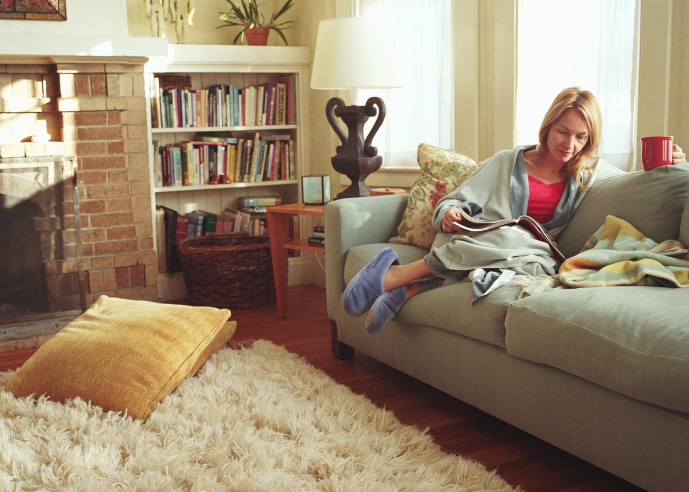 Mulher sentada no sofá a ler