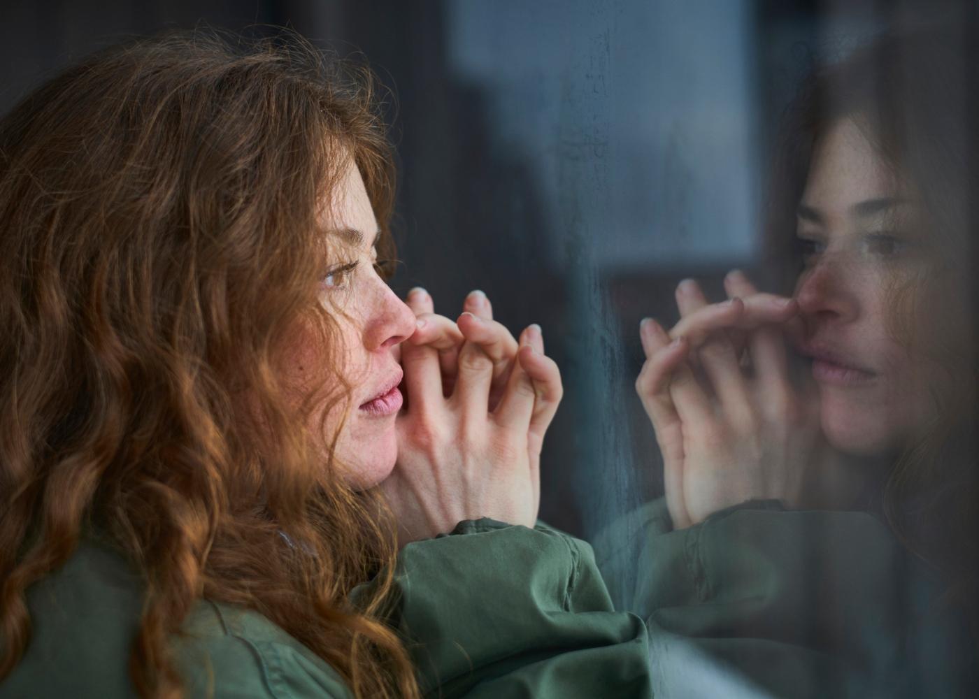 Stress pós-traumático: mulher a olhar pela janela