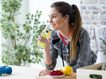 Cuidados a ter para não ganhar peso durante a quarentena: mulher a hidratar-se