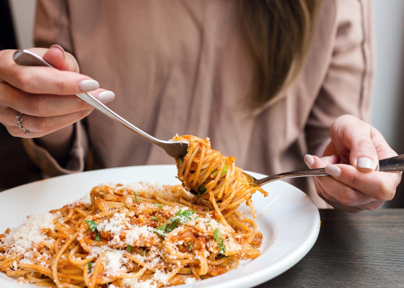 Reduzir a quantidade de hidratos de carbono durante a quarentena: mulher a comer prato de bolonhesa