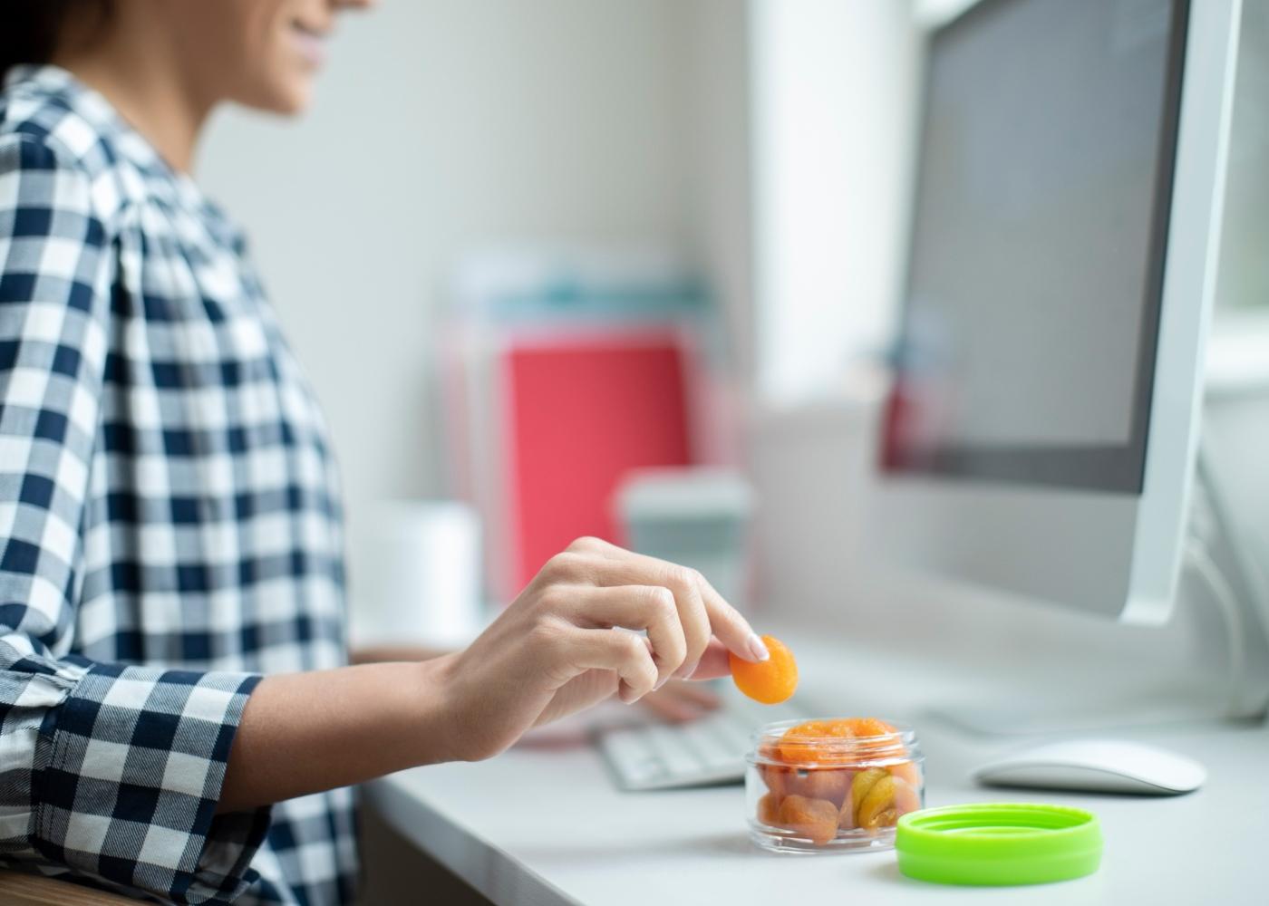 Comer as quantidades que deve em casa: mulher a comer snacks enquanto trabalha