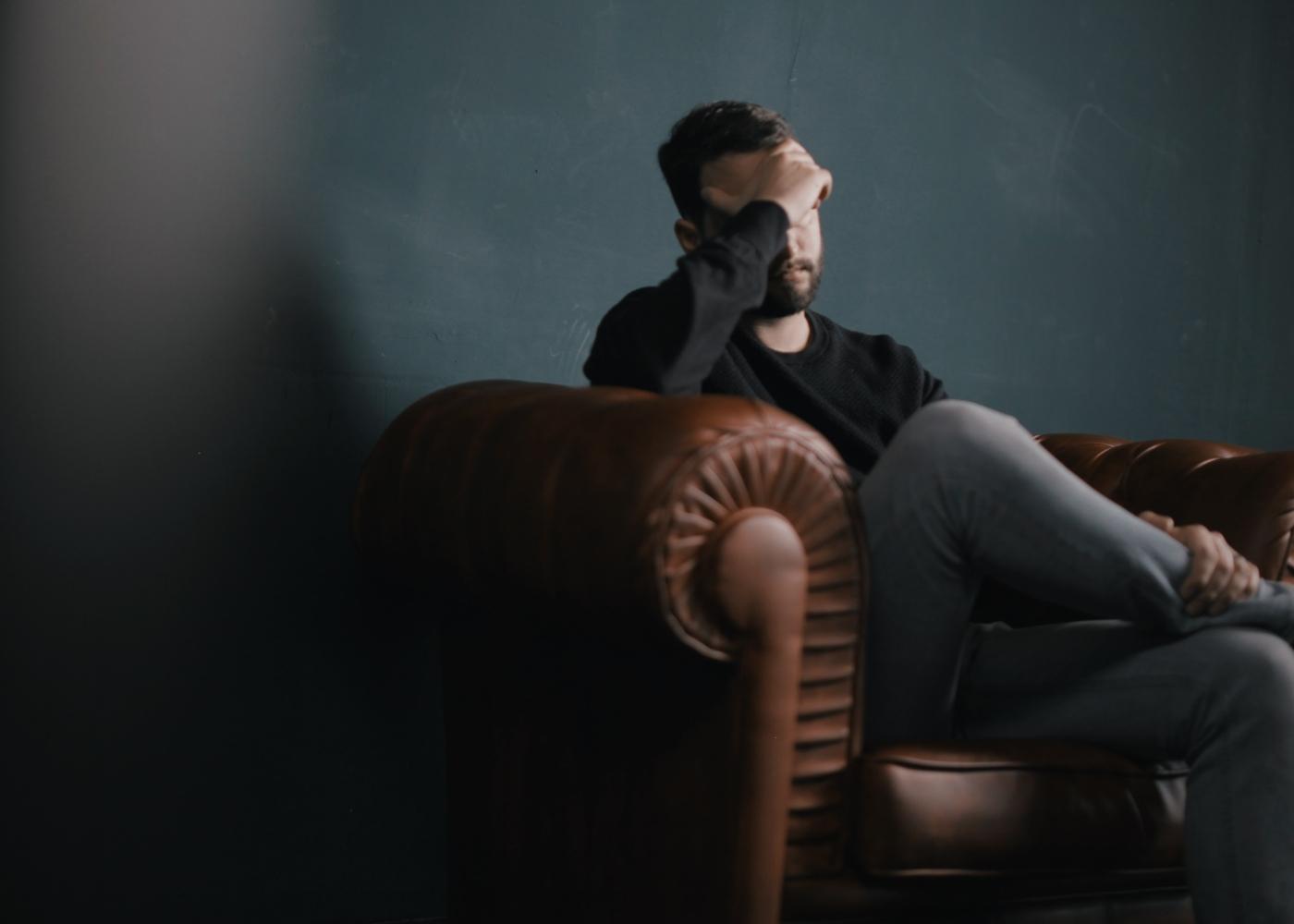 Stress pós-traumático: homem sentado no sofá a pensar