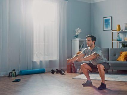 Tipos de agachamentos: homem a treinar em casa
