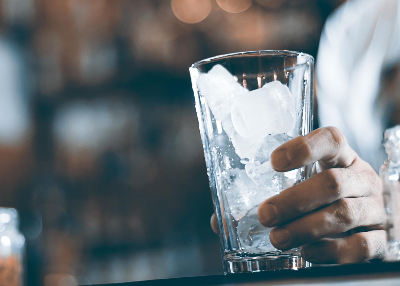Cozinhar de forma segura: homem com copo com gelo na mão