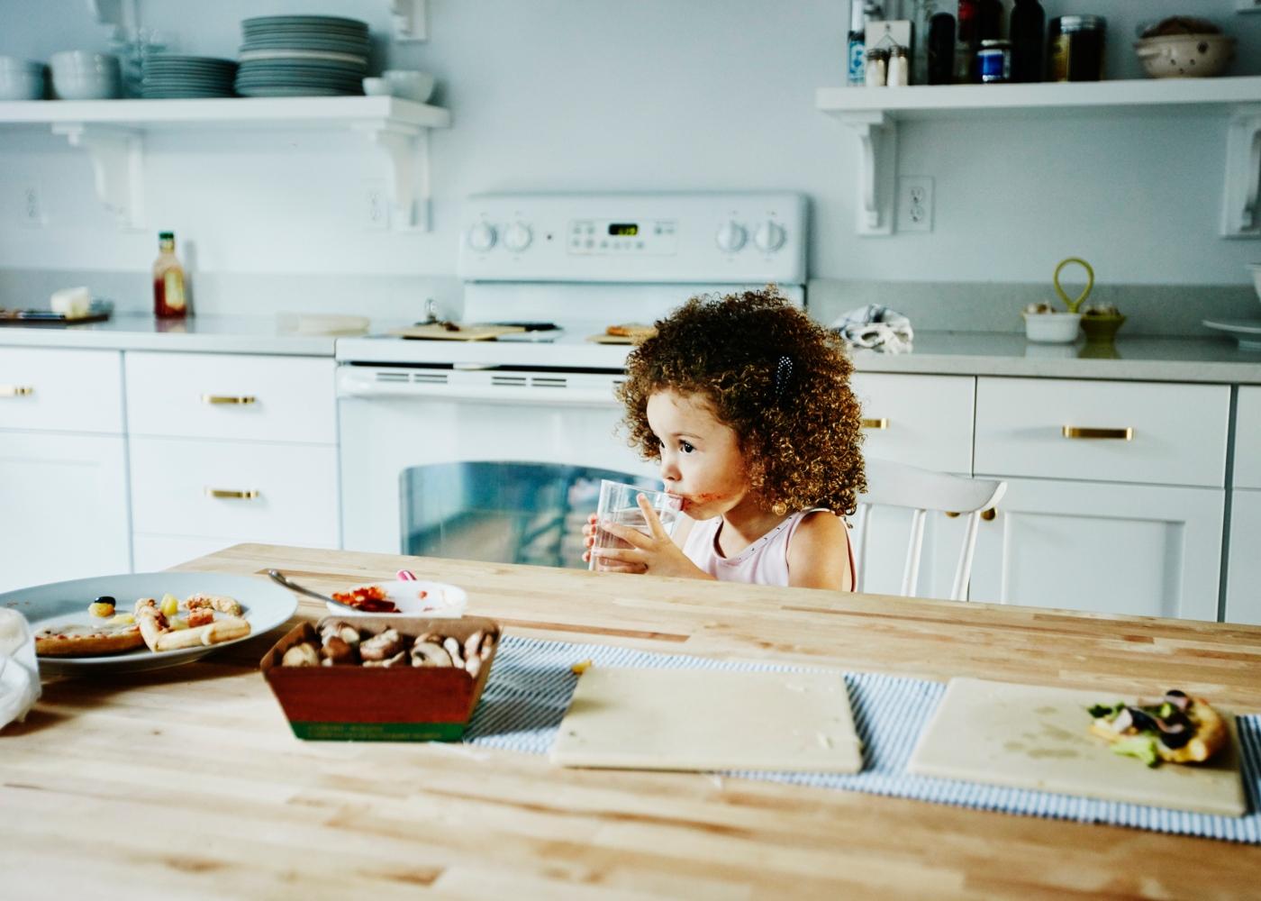 Cuidados alimentares com as crianças: menina a beber água