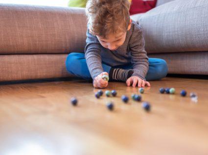 Jogos caseiros para crianças: menino a jogar ao berlinde