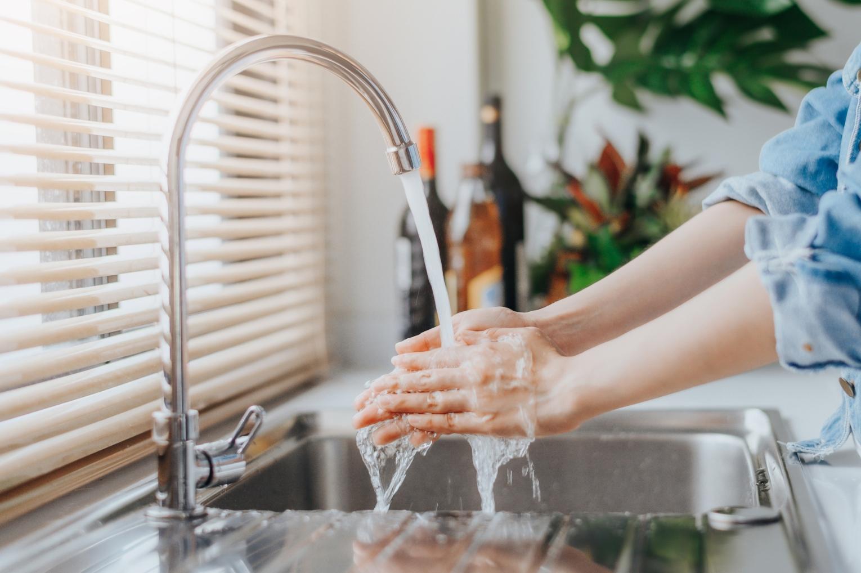 Mulher a lavar as mãos para cozinhar de forma segura