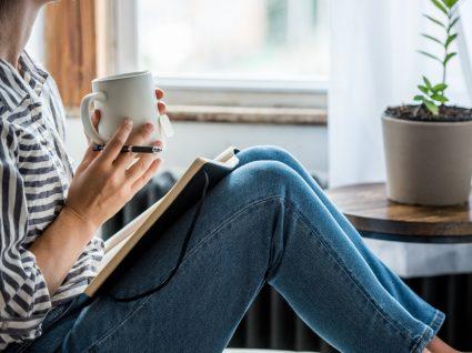 Como lidar com o stress em isolamento social: mulher a escrever no diário e a tomar chá