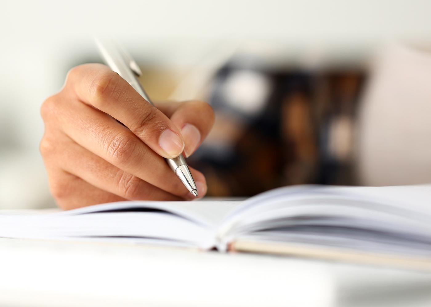 Como lidar com o stress durante o isolamento social: mulher a escrever no diário