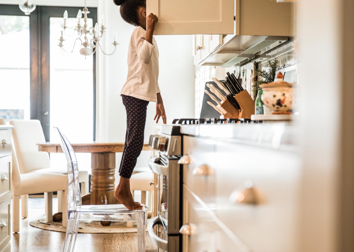 cuidados alimentares com as crianças: menina à procura de bolachas nos armários da cozinha