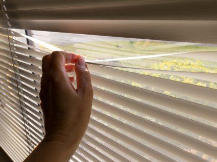 Agorafobia: mulher a espreitar pela janela