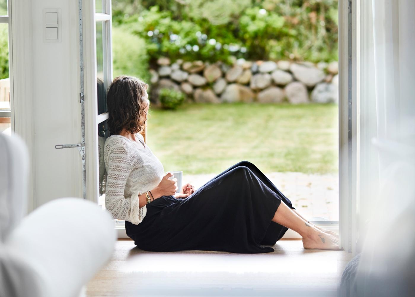 Como lidar com o stress durante o isolamento social: mulher pensativa sentada à porta do jardim de casa