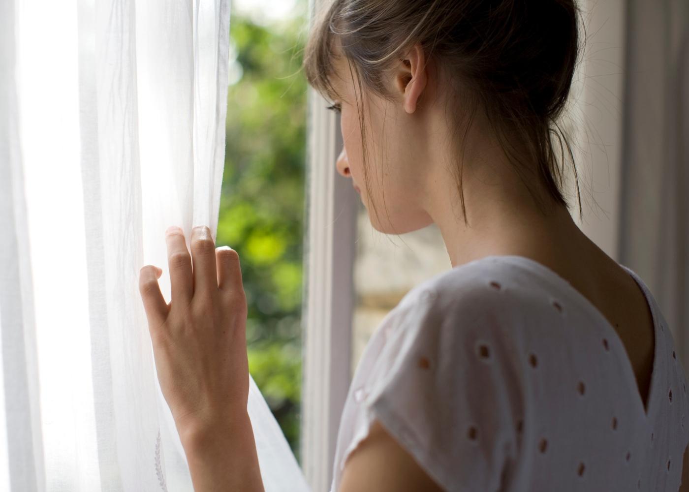 Agorafobia: mulher jovem a espreitar pela janela de casa