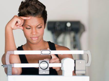 Por que não consigo perder peso: mulher a pesar-se