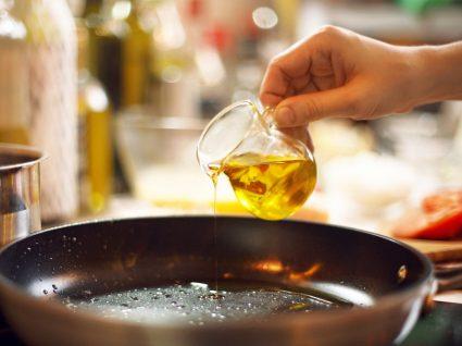 Melhor gordura para cozinhar: mulher a verter óleo para uma frigideira